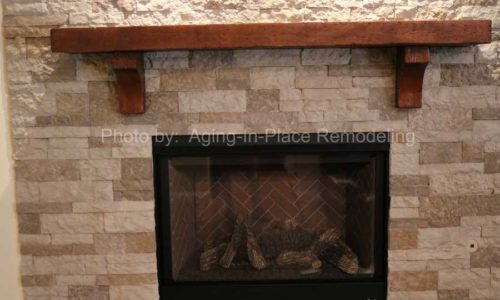 A stone wall creates a beautiful surround for the updated fireplace